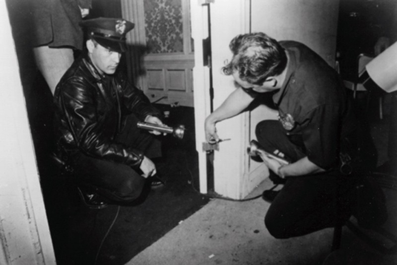 Policemen examine a bullet hole in the doorframe